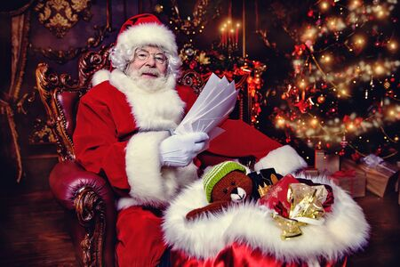 Santa Claus is at his home reading letters with wishes from children. Merry Christmas and Happy New Year. Miracle time. Imagens