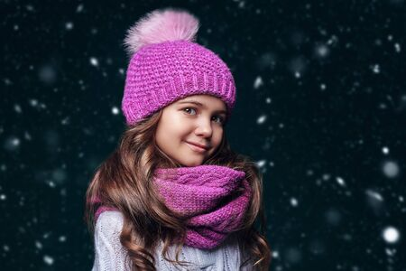Cute girl child wearing knitted hat and a scarf stands under the snow and smiles. Kids fashion. Winter clothes. Merry Christmas and Happy New Year! 版權商用圖片
