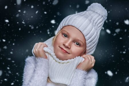 Cute girl child wearing knitted hat and a scarf stands under the snow and smiles. Kids fashion. Winter clothes. Merry Christmas and Happy New Year! Zdjęcie Seryjne