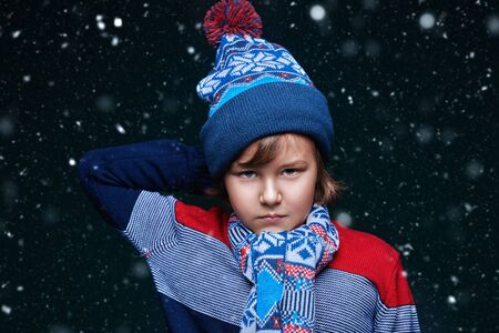 Portrait of a cute emotional boy child in winter clothes under the snow. Kids fashion. Winter clothes. Merry Christmas and Happy New Year!
