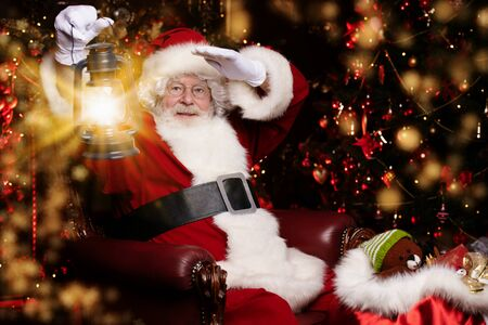 A portrait of Santa Claus sitting at his home with a lantern. Miracle time. Christmas, New Year.
