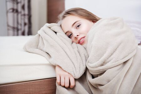 An attractive smiling young girl is sitting wrapped in a blanket on the floor near the bed at home.