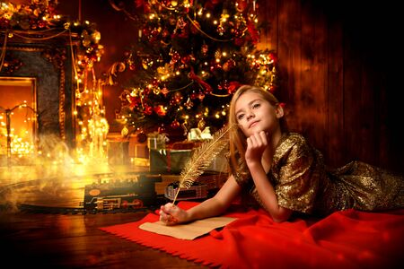 Cute girl is lying and writing a letter to Santa Claus  near the Christmas tree. Christmas concept. Believe in miracles.