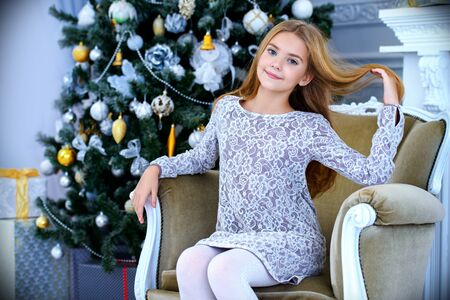 Pretty smiling girl sitting in a armchair in a Christmas room. Merry Christmas and Happy New Year. 免版税图像