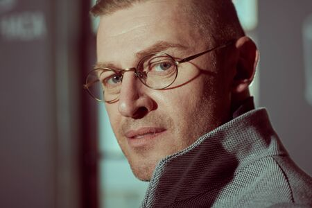 Close-up portrait of a handsome middle aged man in elegant clothes and glasses standing by the window.