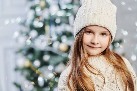 Portrait of a pretty little girl in white knitted hat and sweater against the background of a beautiful Christmas tree. Winter kids fashion.
