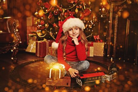 Happy cute girl celebrates Christmas by a beautiful Christmas tree with toys and gifts. The atmosphere of magic, lights and sparkle is around.