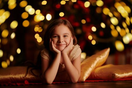 Magic for Christmas. Cute little girl in a cozy atmosphere near a beautiful New Year tree surrounded by golden lights. Christmas Eve.