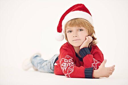 Niño lindo con sombrero de Santa Claus sonriendo a la cámara. Retrato de estudio sobre fondo blanco. Foto de archivo