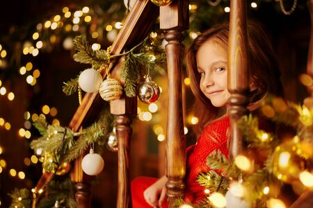 Happy little girl celebrates Christmas in a house beautifully decorated with spruce garlands and New Years toys. The atmosphere of magic, lights and sparkle is around.