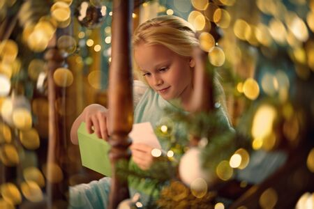 Cute little girl writes a letter to Santa Claus in a house beautifully decorated for Christmas. Zdjęcie Seryjne
