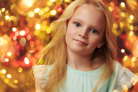 Happy cute girl celebrates Christmas by a beautiful Christmas tree. The atmosphere of magic, lights and sparkle is around. Zdjęcie Seryjne