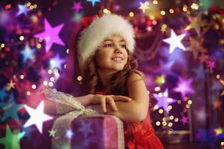 Portrait of a happy cute girl in red dress and Santa Claus hat sitting with a gift box by a beautiful Christmas tree and fireplace. The atmosphere of magic, lights and sparkle is around.