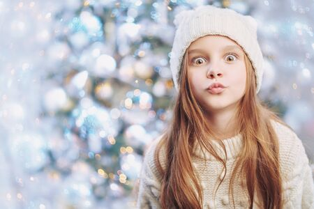 Christmas and New Year concept. Portrait of a funny little girl in white knitted hat and sweater against the background of a beautiful Christmas tree. Winter kids fashion.