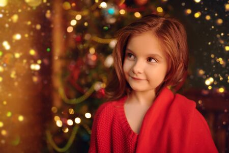Portrait of a happy little girl against the background of a beautiful Christmas tree in a wooden house. The atmosphere of magic, lights and sparkle is around. 版權商用圖片