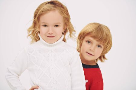 Two cute little kids in knitted sweaters posing together with fun. Studio portrait over white background. Winter kids fashion. Christmas and New Year concept.