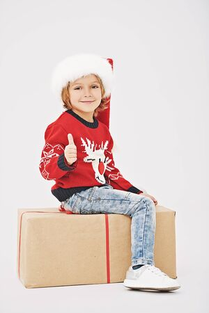 Cute little boy in Santa Claus hat sits on a gift box and smiles at the camera. Studio portrait over white background.
