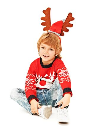 Cute little boy with Christmas deer horns on his head and in a festive red knitted sweater smiles at the camera. Studio portrait over white background. 版權商用圖片