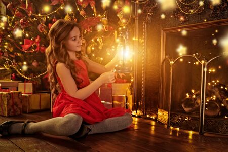 Happy cute girl in red dress celebrates Christmas by a beautiful Christmas tree and fireplace. The atmosphere of magic, lights and sparkle is around.