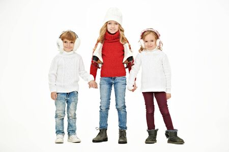 Three beautiful kids in winter clothes posing together at studio. White background. Winter fashion, winter activities. Christmas and New Year.