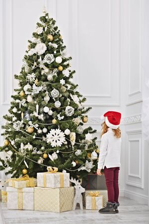 Christmas and New Year concept. Happy little girl in Santa Claus hat turned her back to the camera and looks at a beautiful Christmas tree with gifts and toys.