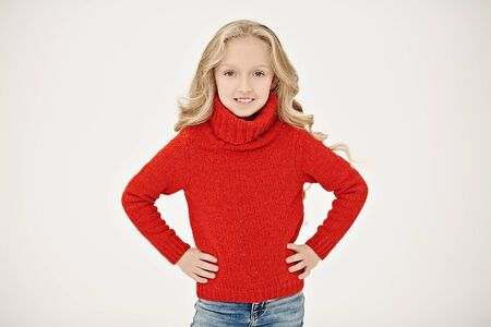 Portrait of a pretty child girl with beautiful blonde hair smiling at camera. Christmas red sweater. White background. Winter kids fashion. Christmas and New Year concept.