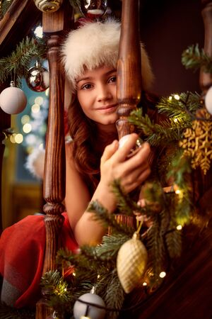 Christmas and New Year concept. Happy little girl celebrates Christmas in a house beautifully decorated with spruce garlands and New Years toys. The atmosphere of magic.