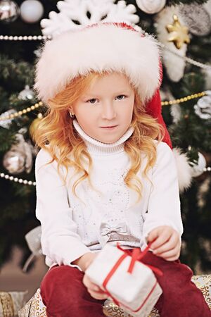 Christmas and New Year concept. Sad little girl holds a small box with gifts. Holiday disappointment. Beautiful Christmas tree in the background.