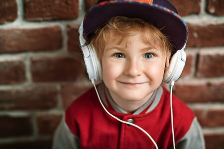 A portrait of a young schoolboy posing in the studio over the brick wall and listening to music in the headphones. Kids casual fashion, education. Stockfoto