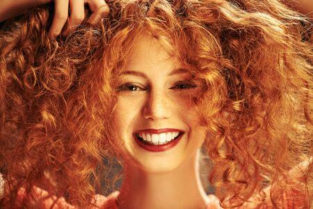 Feliz niña riendo disfruta de su hermoso cabello rizado rojo. Retrato de primer plano. Cuidado del cabello, coloración del cabello. Foto de archivo
