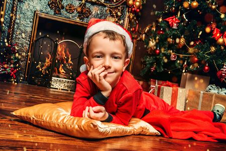 A portrait of a young boy on the pillow on the floor at home. Merry Christmas and Happy New Year. Time for miracles. Imagens