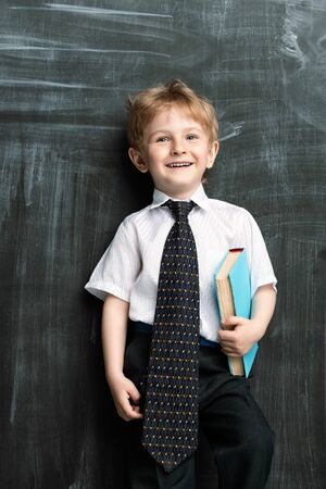 A portrait of a young schoolboy near the blackboard with books. Kids fashion for school, elementary school, education.