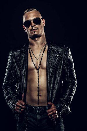 Retrato oscuro de un hombre punk serio con chaqueta de cuero negra. Foto de archivo