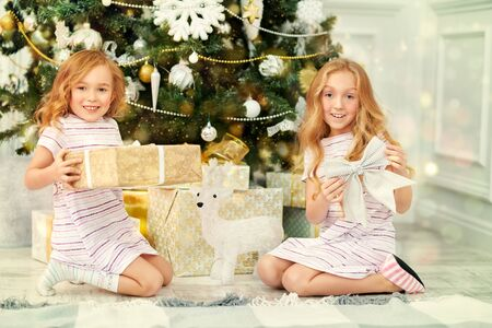 Merry Christmas and Happy New Year! Two happy girls sisters sit near the Christmas tree and open gift boxes.