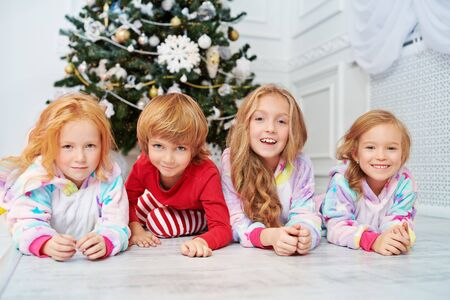 Merry Christmas and Happy New Year! Happy children are lying under the Christmas tree waiting for Santa Claus and gifts.