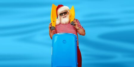 Jolly Santa Claus goes on vacation to the sea. Christmas Holidays, tourist trips to hot tropical countries. Blue background. Copy space.