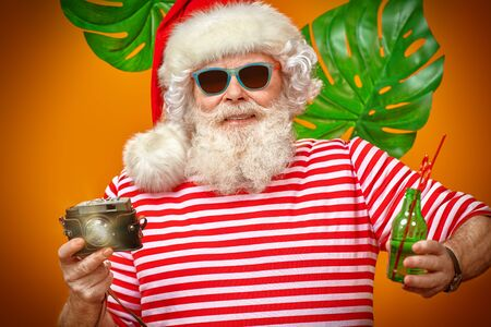 Joyful Santa Claus is relaxing and taking pictures in hot tropical countries. Christmas Holidays, tourist trips to the sea. Bright yellow background. Zdjęcie Seryjne