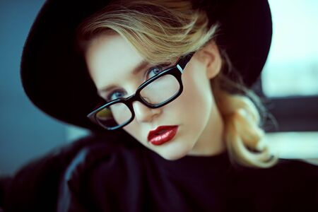 Close-up portrait of a fashionable young woman in modern glasses and hat in interiors. Beauty, fashion concept. Optics, eyewear. Copy space.