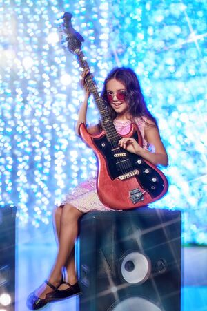 Christmas and New Year kid's party. Cool little girl plays the guitar an electric guitar next to the speakers. Disco and lights.