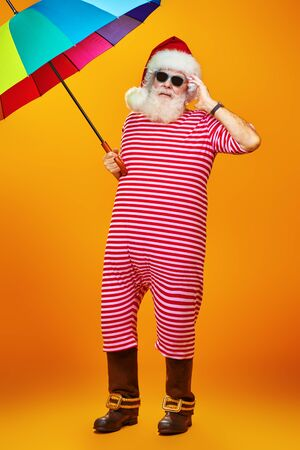 Portrait of Santa in a swimming suit with a rainbow umbrella. Winter holidays in warm countries. Merry Christmas.