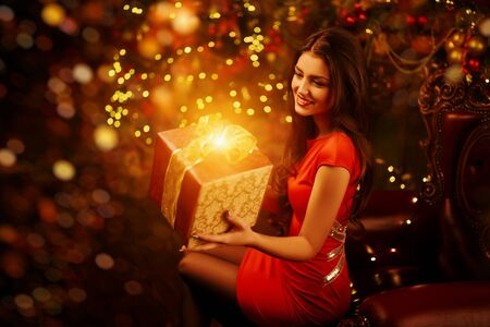 Christmas and New Year concept. Beautiful happy girl celebrates Christmas in the fairy Christmas interior with lights around. Christmas tree and fireplace in the background. Фото со стока