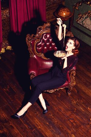 A full length portrait of a beautiful woman posing in the vintage interior and having a meal. Beauty, fashion, interior.
