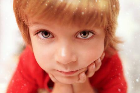 Cute little boy looking at camera. Studio portrait over snowy background. Stock fotó
