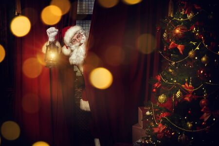 Jolly Santa Claus sneaks into the house through the window, he looks out from behind the curtains with a lantern. Christmas and New Year concept. Stock Photo