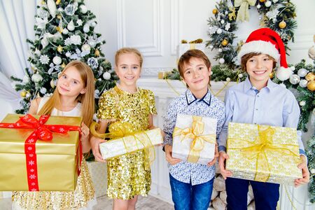 Four happy children in elegant clothes are holding gifts in their hands. Beautiful room decorated for Christmas. Kid's fashion concept. Merry Christmas and Happy New Year.