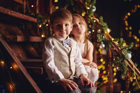 Two cute children boy and girl in beautiful festive clothes in a romantic Christmas atmosphere Christmas and New Year concept.