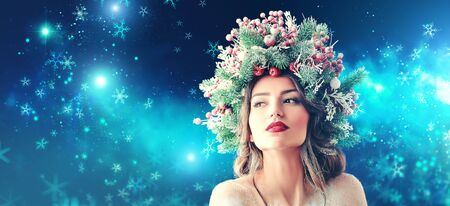 Christmas magic. Beautiful young woman with a Christmas spruce wreath on her head on snow background. Stock Photo