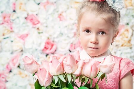 A close up portrait of a pretty child girl posing in the studio over the background with flowers. Kids, summer, beauty.
