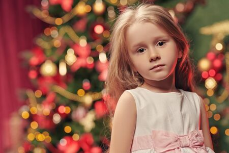 Portrait of a happy little girl at home with a beautiful Christmas tree in the background. The atmosphere of magic, lights and sparkle is around.