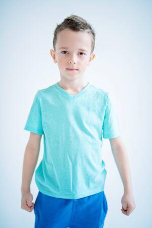 Un retrato de un niño guapo posando en el estudio sobre el fondo azul. Niños, moda, estilo casual, belleza.